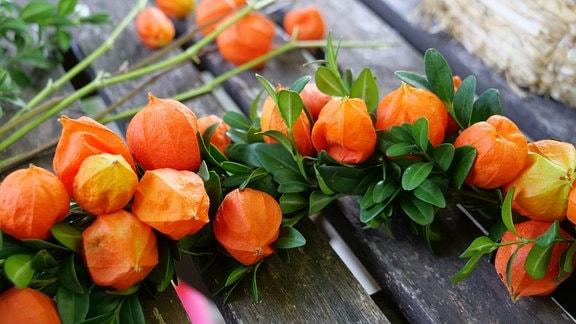 Ein Dekokranz aus Lampionblumen und Buchstrieben. Nahaufnahme.