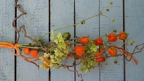 Dekoration aus Lampionblume, abgeblühter Herbstanemone, Hortensienblüten und einem Korkenzieherhasel-Zweig.