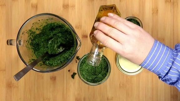Eine Hand gießt aus einer kleinen Glasflasche gelbes Öl in ein rundes Gefäß mit einer grünen Paste aus gehackten Kohl-Blättern, das neben einer etwas größeren Glaskanne mit grüner Paste auf einer Tischplatte aus Holz steht