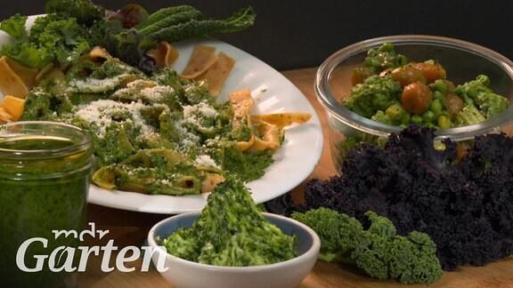 Ein Glas mit Kohl-Paste, eine Teller Bandnudeln mit grüner Soße, ein Schälchen grüner, mit Kohlpaste versetzter Butter und eine Schale mit Gemüse sowie grüne und dunkellila Kohlblätter auf einer Tischplatte aus Holz