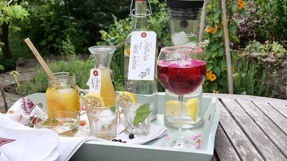 Verschiedene getränke stehen auf einem Tablet auf dem Tisch in einem Garten
