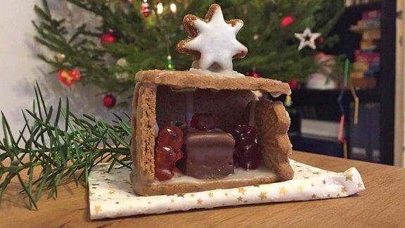 Ein selbst gebautes Pfefferkuchenhaus steht auf einem Tisch