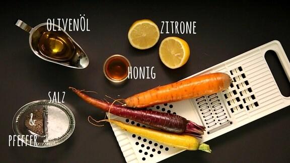 Olivenöl, Zitone, Honig, Salz und Pfeffer, Möhren und eine Reibe auf einem Tisch.