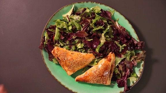 Blätterteigtaschen, Salat und Gemüse liegen auf einem Teller.