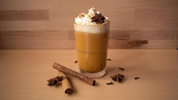 Pumpkin Spice Latte mit Sahne und Gewürzen in einem langen Glas auf einem Holztisch