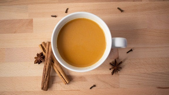 Pumpkin Spice Latte in einer weißen Tasse auf einem Holztisch mit Gewürzen.