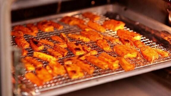 Pommes aus Süßkartoffeln auf einem Backblech mit Gitter
