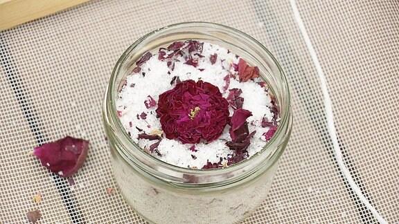 Getrocknete Rosenblüten liegen auf Salz in einem geöffneten Schraubglas