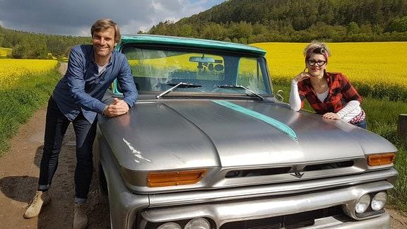 Gartenreporter Norbert Rossbach und Floristin Franziska Rühle lehnen an der Motorhaube eines Oldtimers.