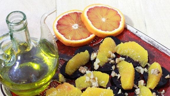Rote Bete, Orangen und Walnüsse sind zu einem Salat verarbeitet und liegen auf einem Teller, daneben steht Olivenöl.