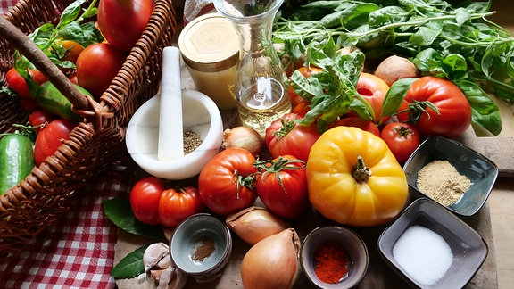 Gelbe und rote Tomaten liegen mit Zwiebeln und Gewürzen auf einem Tisch