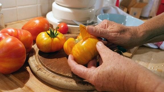 Haut einer gelben Tomate wird mit dem Messer abgezogen