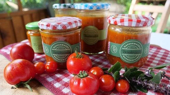 Mit Tomatensoße gefüllte Gläser auf einem Tisch