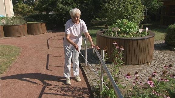 Besucherin im Blindengarten Radeberg orientiert sich an Handläufen neben Hochbeeten