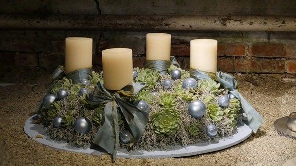 Adventskranz mit Sukkulenten, eisblauen Weihnachtskugeln und weißen Stumpenkerzen