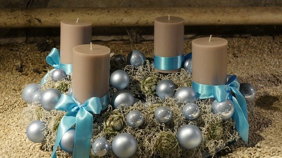 Adventskranz mit Sukkulenten, eisblauen Weihnachtskugeln und braunen Stumpenkerzen