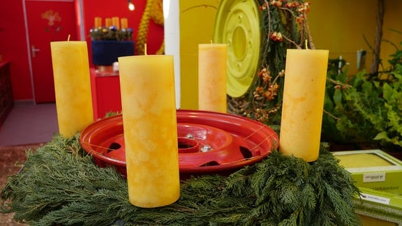 Adventskranz um eine rote Felge mit gelben Stumpenkerzen