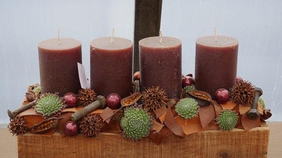 Adventskranz mit Leder, rostigen Schrauben, Sukkulenten, Hülsen und rotbraunen Stumpenkerzen