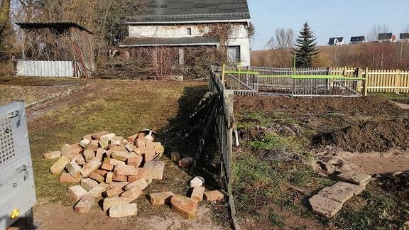 Baustelle in einem Garten. Neben einem alten Zaun liegen Ziegelsteine.