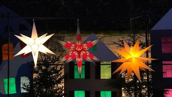 Herrnhuter Stern und zwei andere Faltsterne leuchten im Dunklen