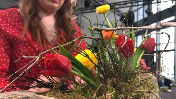Mit Tulpen und Zweigen dekoriertes Gefäß aus Holz