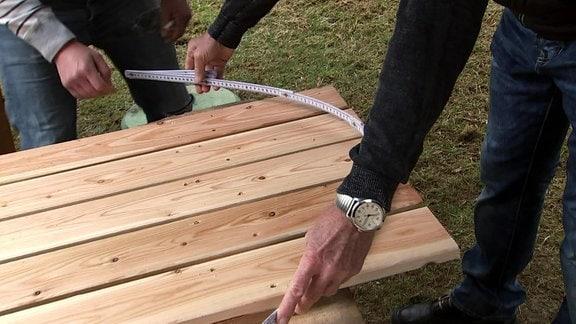 Mit einem Zollstock wird ein Halbkreis auf Bretter aufgemalt.