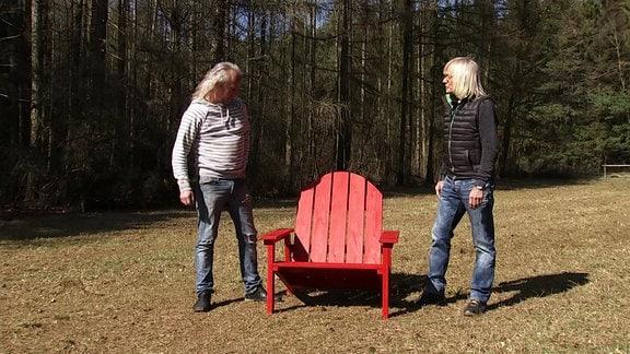 Zwei Männer stehen neben einem roten Stuhl aus Holz.