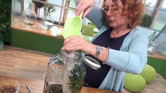 Gartenexpertin Brigitte Goss füllt Erde in ein großes Glas.