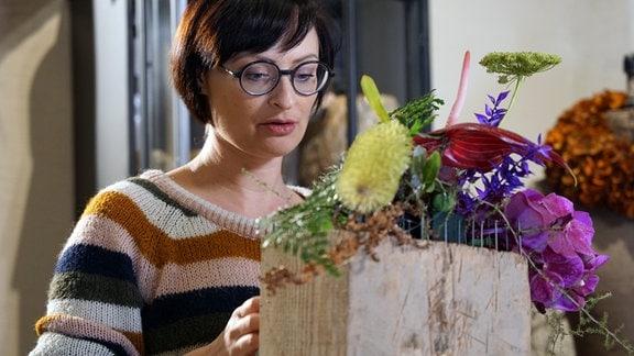 Floristin Juliane Müller arbeitet an Holzblock mit Nägeln und exotischen Pflanzen