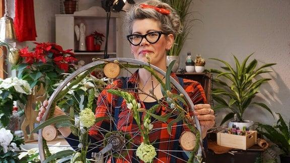 Floristin Franziska Rühle zeigt Fahrrad-Felge mit Deko aus Blumen und Zweigen