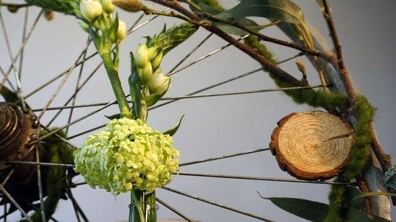 Fahrrad-Felge mit Deko aus Blumen und Zweigen