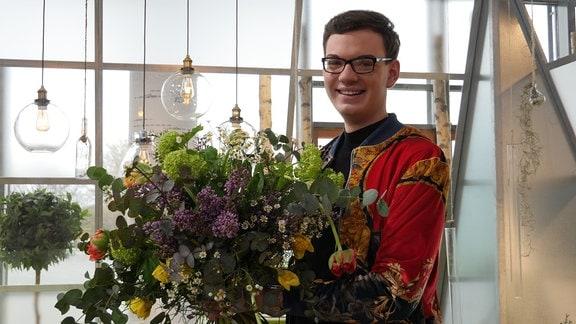 Florist Quentin Oberstedt hält seinen Blumenstrauß.