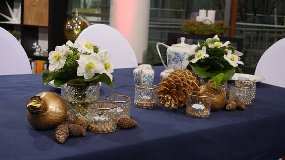 Ein für ein Kaffeetrinken gedeckter Tisch mit zwei Christrosen-Sträußen, Teelichtgläsern, gold gewachsten Amaryllisknollen sowie verschiedenen Zapfen.