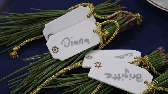 Vier Bündel Kiefernnadeln mit Goldband und Namenschildchen aus Porzellan liegen auf einer blauen Tischdecke.