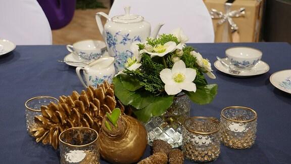 Weihnachtliche Blumendekoration auf einem gedeckten Kaffeetisch: Ein Strauß Christrosen steht in einer Glasvase.  Außerdem stehen Teelichtgläser neben Zapfen und einer Amaryllisknolle.