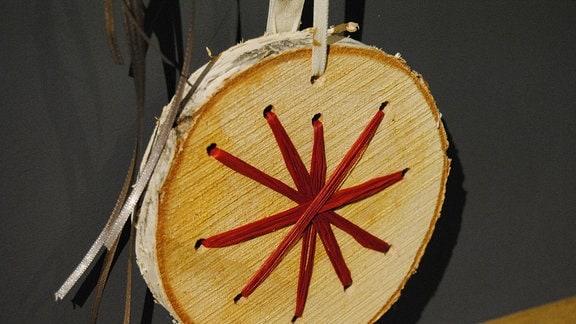 Baumstamm-Scheibe mit sternförmig durchgefädeltem Band