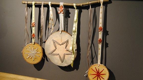 Hängende Weihnachtsdekoration mit Baumstamm-Scheiben und Bändern