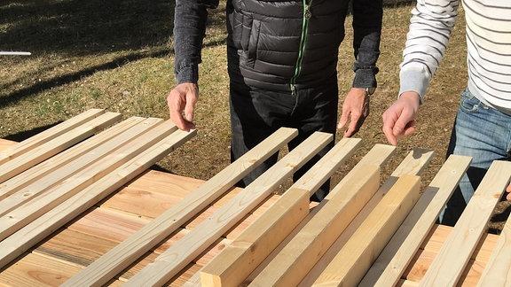 Holzlatten liegen nebeneinander auf einem Arbeitstisch.