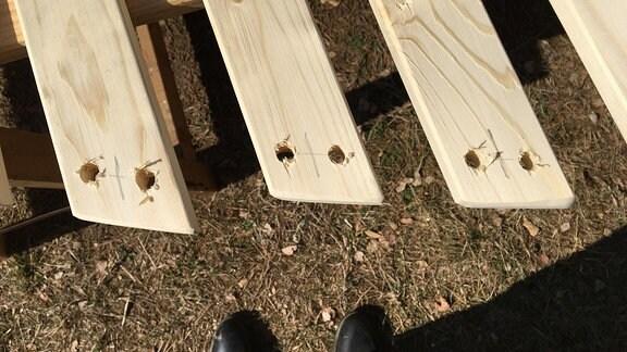 Am Ende einer Holzlatte befinden sich zwei Bohrlöcher.