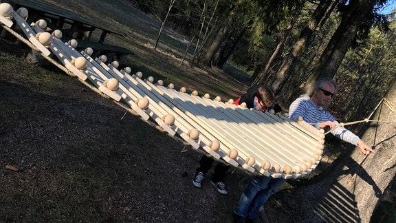 Hängematte aus Holzlatten ist an Baum befestigt.