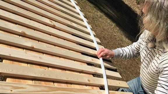 Ein Mann arbeitet an Hängematte aus Holz.