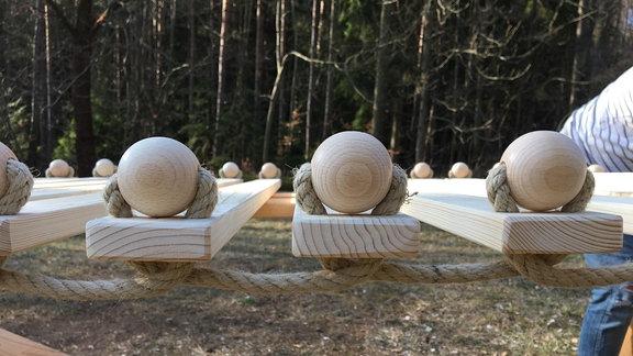 Mit einem Seil verbundene Holzlatten und Holzkugeln.