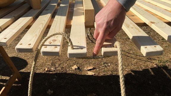 Ein Seil wird durch ein Loch in einer Holzlatte gezogen.