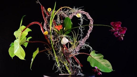 Mit Orchidee und Blättern dekoriertes, geflochtenes Herz