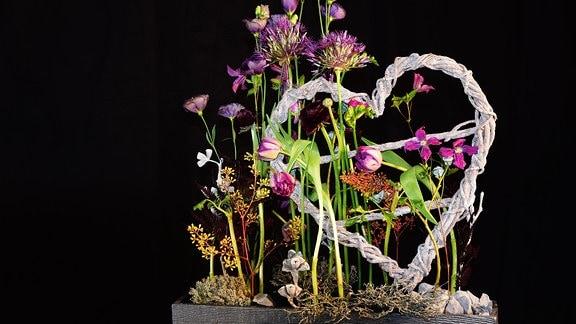 Mit lila Blumen dekoriertes, geflochtenes Herz
