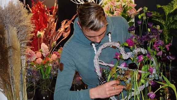 Florist Martin Neumann dekoriert ein geflochtenes Herz