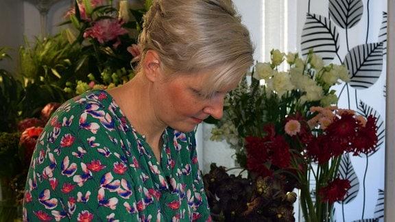 Floristin Stefanie Krumbholz dekoriert ein geflochtenes Herz