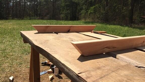 Auf einem Holztisch liegen zwei an den Enden angeschräckte Holzlatten.