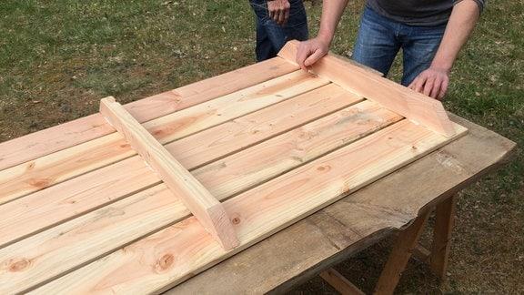 Auf einem liegen fünf Holzleisten. Darauf steht zwei weitere Holzlatten. Zwei Personen sind im Hintergrund angeschnitten zu erkennen.
