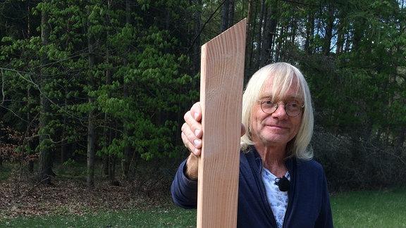 Ein Mann hält eine Holzlatte die an den Enden parallel zueinander angeschrägt sind.